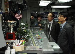 US Navy 111214-N-JO245-059 Lt. Cmdr. Dave Hecht gives a tour of flight deck control aboard the Nimitz-class aircraft carrier USS George Washington.jpg