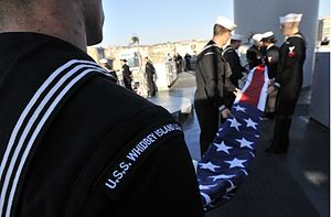 US Navy 120117-N-AG285-180 Sailors aboard the amphibious dock landing ship USS Whidbey Island (LSD 41) fold the American flag after arriving at Nap.jpg