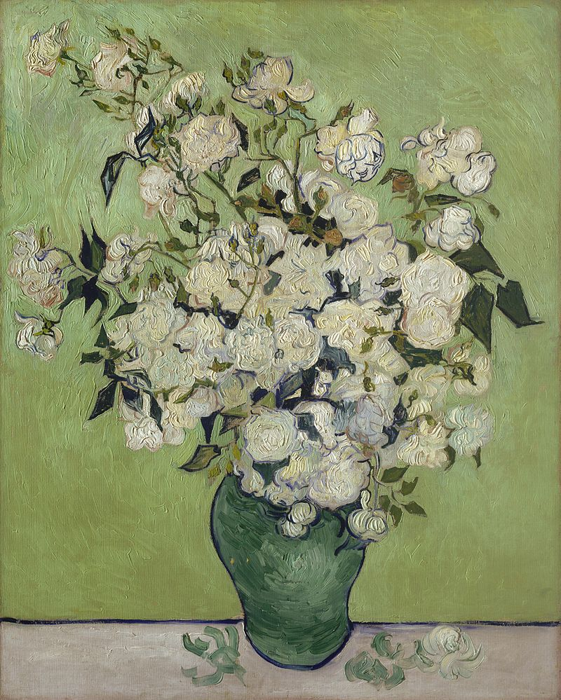 Pale pink roses in a green vase, against a pale green background.