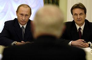 Russian President Vladimir Putin, left, speaks...