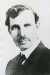 A black and white picture of a man in a suit with a large mustache