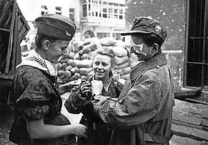 "Jan Mazurkiewicz - Soldiers of the ''Parasol'' battalion after emerging from sewers at Warecka Street. Center: Maria Stypułkowska-Chojecka ""Kama"", right: Krzysztof Palester ""Krzych""."