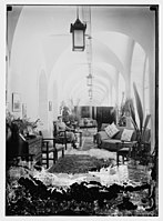 Woman seated in room decorated with rugs and pictures LOC matpc.10469.jpg
