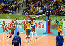 Brazilian and Cuban athletes during a volleyball match wearing the official uniforms of their respective nations. The audience remained watching at the competition venue for the volleyball tournament.