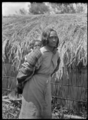 Young Maori woman carrying a child on her back, standing outside a whare thatched with palm fronds, at Rangiahua, 1918. ATLIB 296721.png