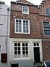 foto van Huis met rechte gevel van rode baksteen. In het metselwerk gele banden en gele blokken in de ontlastingsbogen boven de vensters. Stoeptrapje
