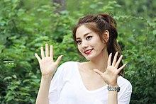 Nana trägt ein weißes Kleid, lächelt und winkt mit beiden Händen vor grünem Hintergrund