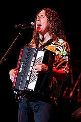 "A photograph of ""Weird Al"" Yankovic, singing through a microphone and playing a harmonica."