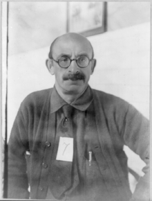 A 49-year-old man with a balding head wearing a pair of glasses