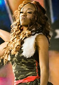 An African-American woman with dark curly hair, wears a camouflage dress with a red belt and white fur trim on the shoulders.