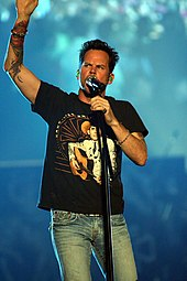 A man wearing a black t-shirt and blue jeans singing into a microphone