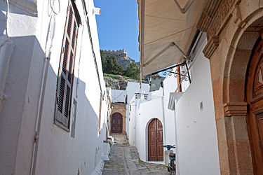 Alley in Lindos, Rhodes with the acropolis in the background.jpg
