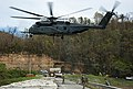 An MH-53E helicopter transports a concrete barrier to help repair the Dam in Puerto Rico. (37584332832).jpg