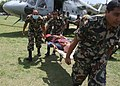 An injured person on a stretcher, carried by the Nepalese Army after being evacuated by an IAF Mi-17 helicopter from a quake-hit area in Nepal.jpg