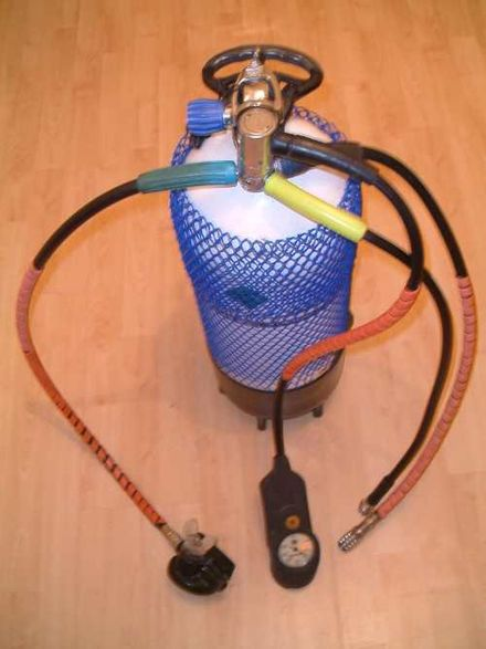 A single-hose regulator with 2nd stage, gauges, BC attachment, and dry suit hose mounted on a cylinder Aqua lung.jpg