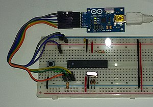 Jump wire - Jump wires at the end of a multi-colored ribbon cable are used to connect the pin header at the left side of a blue USB2Serial board to a white breadboard below. Another jumper cable ending in a USB micro male connector mates to the right side of the USB2Serial board. Red and black tinned jump wires can be seen on the breadboard.
