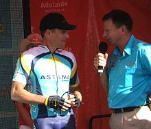 A man in his late thirties in a blue and white cycling jersey with yellow trim stands next to a man in his mid-fifties wearing a light blue collared shirt and holding a microphone. They stand in front of a red backdrop, and a woman in a cowboy hat is partly visible behind the cyclist.
