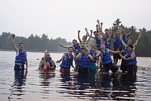 Summer camp - Attendees of summer camps often enjoy outdoor activities. This photo of a YMCA camp shows campers in a lake.