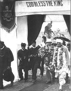 A group of Western-clad Indians in turbans escort a Western dignitary holding a flower bouquet in hand