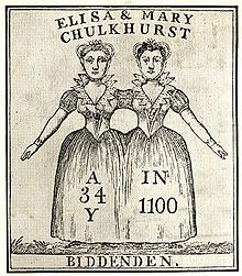 Two women, apparently joined at the shoulder. The women are wearing a single skirt between them. The women's facial features and hair colours are not identical.