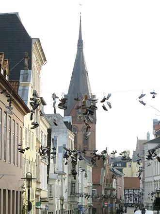 """Shoe tossing - Because of the Shoefiti the Norderstraße (Northern Street) in Flensburg, Germany, is named by the New Yorker travel magazine Travel + Leisure to one of the """"World's Strangest Streets""""."""