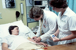 Doctor–patient relationship - The medical doctor, with a nurse by his side, is performing a blood test at a hospital in 1980.
