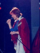 Bowie with red hair man looking to the left holding a microphone and wearing a red and white fur coat