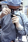 A doctor using a flexible fiberoptic bronchoscope to explore the airways.
