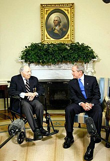 An old man in a wheel chair is talking to a middle-aged man sitting to the right. In the background, above their heads are a plant decoration and a portrait of some historical person.