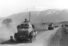 an eight-wheeled armoured car on a dirt road with other vehicles in the background