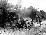 This German armored vehicle was destroyed by an American tank near Saint Aubin, the burning remains are inspected by US soldiers.