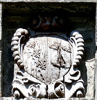Colleton, Chulmleigh - Heraldic escutcheon above the front door of Colleton Barton, showing the arms of Bury of Colleton: Ermine, on a bend engrailed azure three fleurs-de-lys or impaling Bere of Huntsham: Argent, three bear's heads erased sable muzzled or