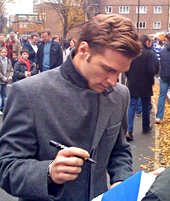 A man wearing a dark grey woollen coat signs an autograph outside for a fan.
