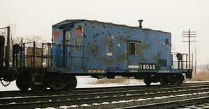 Conrail - Conrail transfer caboose 18065 brings up the rear of a local freight passing Porter, Indiana, in the early 1990s
