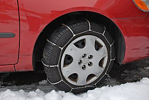 Snow chains - Cable chains on a car tire, with a relatively simple and easy-to-secure design; this is a ladder-type design