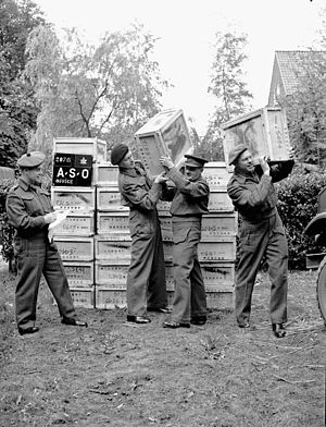 The Lorne Scots (Peel, Dufferin and Halton Regiment) - Delivery of 500,000 free cigarettes from the Overseas Tobacco League to the 5th Canadian Armoured Division, Groningen, Netherlands; (L-R): Captain J.F. Yeddeay, Lorne Scots; Senior Supervisor W.R. Blythman and Supervisor R.R. Jacks, both of Canadian Legion Auxiliary Services