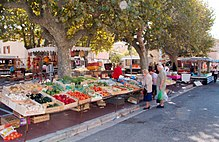 Outdoor scene showing market stalls full of a bright fruit and vegetables