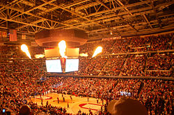 Indoor arena with people lighted by fire.