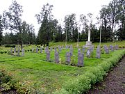 Colour photo of a small graveyard with about 40 dark grey gravestones