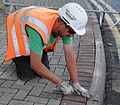 Contractors level sidewalk, ensures safety for pedestrians 140807-F-FE537-019.jpg