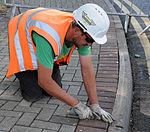 Contractors level sidewalk, ensures safety for pedestrians 140807-F-FE537-019.jpg