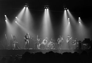 A monochrome image of Pink Floyd performing on a concert stage. Each band member is illuminated from above by bright spotlights