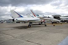 Side view of white jet aircraft parked with other aircraft in the background