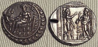 Datames - Silver coin of Datames. Obv:The God Baaltars on a throne, seated left, torsos facing, holding grapes, grain ear, and eagle in right hand, scepter in left hand, surrounded by the city walls. Rev: The God Ana, naked, and Datames, face-to-face.