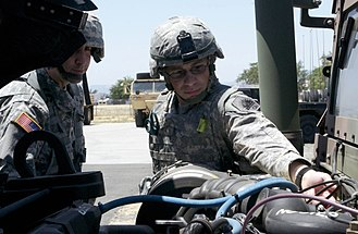 California State Military Reserve - WO1 Joshua Zollo, a firefighter who serves with Alpha Company, 1st Special Troops Battalion, Regional Support Command North, California State Military Reserve, checks under the hood of a Humvee.