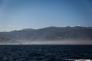 Wetar Strait - Mountains of Díli and boats, seen from the sea.