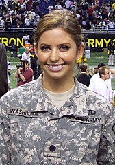 A bust photo of a white woman with brown hair; she is wearing a grey, camouflage US Army uniform and smiling into the camera