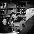 Een van de mannen staat aan de bar terwijl de barkeeper en barkeepster een blikj, Bestanddeelnr 252-9498.jpg