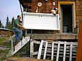 FEMA - 41676 - CRWRC Volunteer and FEMA Logistics Employee Bring a Door into a House.jpg