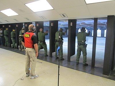 An indoor firing (shooting) range of U.S. federal law enforcement personnel. A range master is shown supervising typical firearms training exercises.